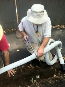 Cutting the agricultural pipe to fit the length of the trench; note the geofabric overing the pipe